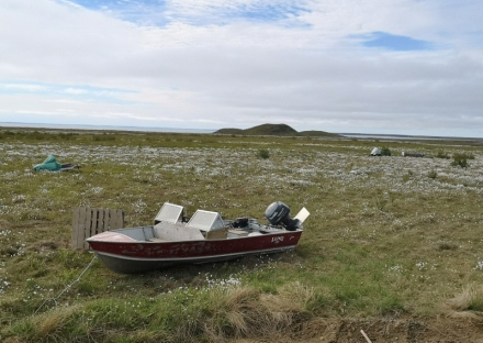 Boats, snomobiles, sleds, with Pingos in the distance