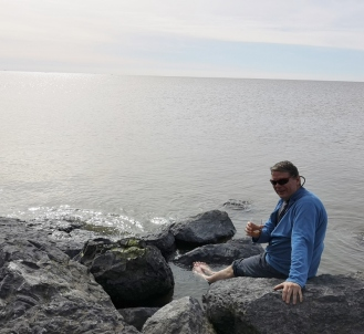Joel drinks a dram with his feet in the Artic Ocean