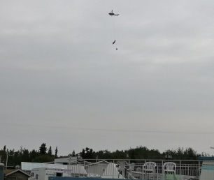 Fire Helicopter and bucket going by and Eagle flying in between