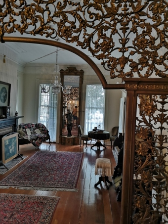 Ornate wood arch frame and massive mirror at the far end and windows you could walk out of.