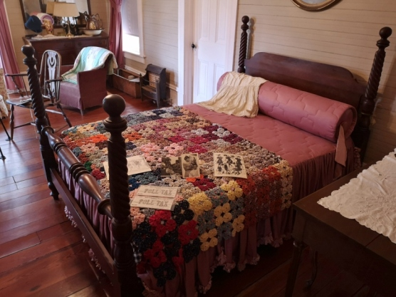 "Bed with ""Yoyo quilt"". Pine flooring made with trees from the property."
