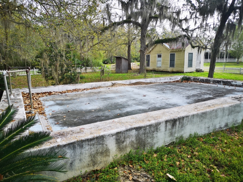 6' cement swimming pool (filled in) and outhouse and Post Office building in background